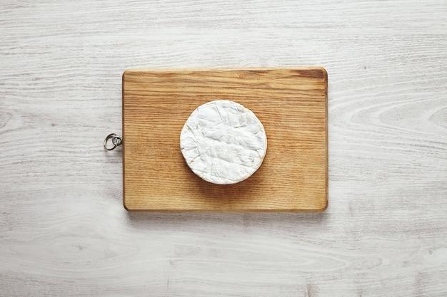 Vista dall'alto del cerchio perfetto di formaggio camembert sulla tavola di legno rustica isolata sulla tavola di legno bianca invecchiata nel centro