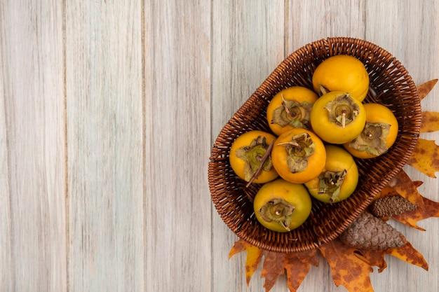 Vista dall'alto di frutti di cachi su un secchio su un tavolo di legno grigio con spazio di copia