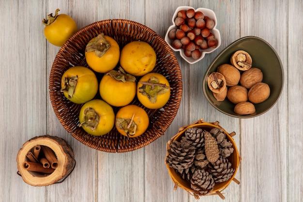 Vista dall'alto di frutti di cachi su un secchio con pigne su un secchio con nocciole su una ciotola con bastoncini di cannella su un tavolo di legno grigio