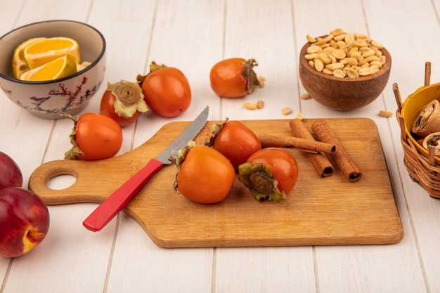 Top view of persimmons on a wooden kitchen board with cinnamon sticks with knife with peanuts on a wooden bowl with peaches isolated on a white wooden background