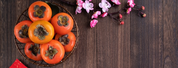 Top view of persimmons on wooden table background for chinese new year