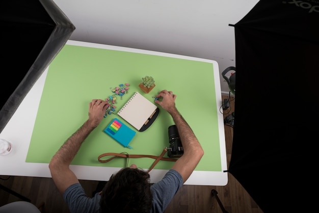 Top view of a person arranging stationery over table near camera and succulent plant in studio