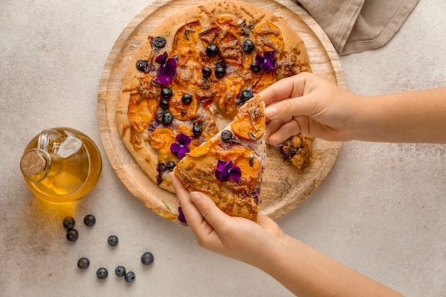 Top view of person grabbing slice of pizza with blueberries and flower petals