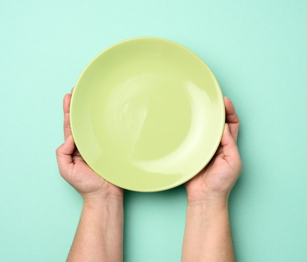Вид сверху человека, держащего круглую пустую зеленую тарелку