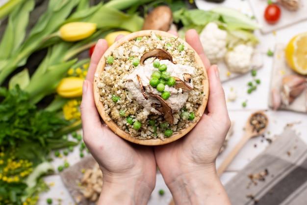 Vista dall'alto di una persona che tiene una ciotola di deliziosa insalata vegana