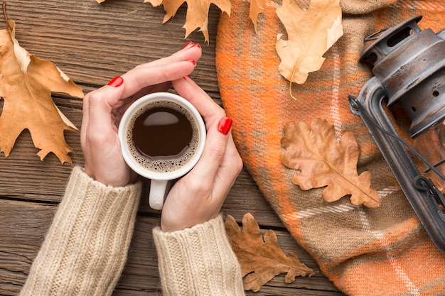 Top view of person holding coffee cup with autumn leaves and lantern