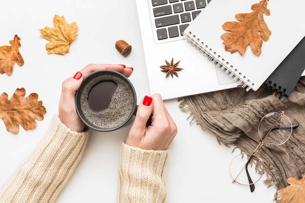 Top view of person holding coffee cup with notebook and laptop