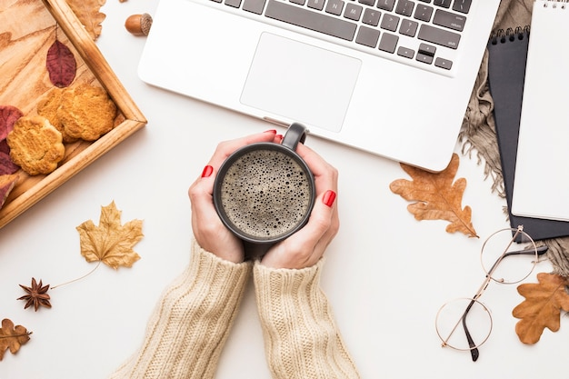 Top view of person holding coffee with laptop and autumn leaves