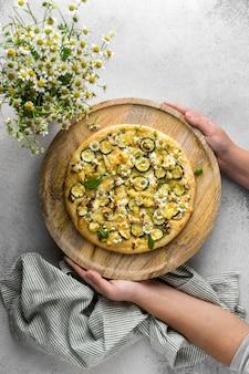 Vista dall'alto della persona che tiene una deliziosa pizza cotta con bouquet di fiori di camomilla