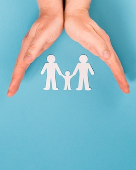 Top view person holding in hands cute paper family with copy space