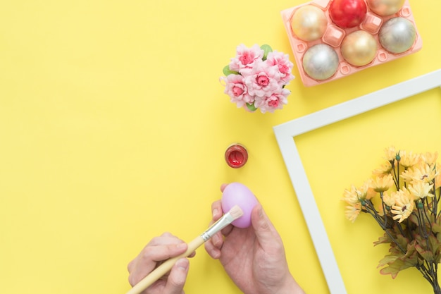 Top view person painting colorful easter egg painted in pastel colors composition with paint brush