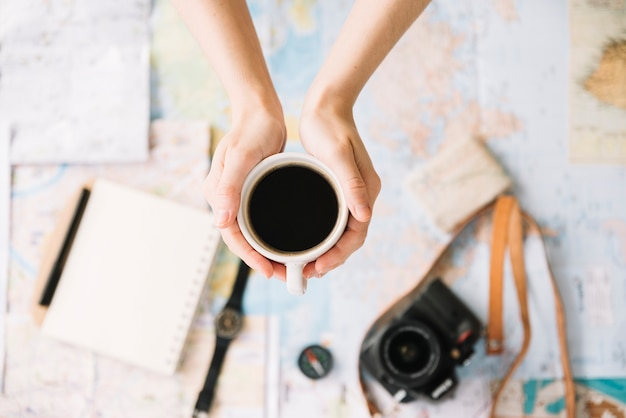 Top view of a person's hand holding coffee cup over the blurred world travel map
