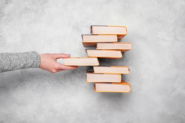 Top view of person stacking hardback books