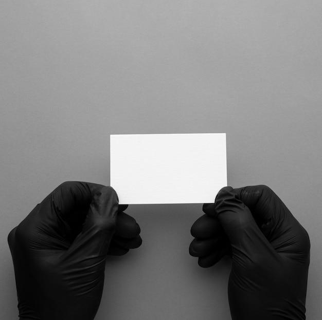 Вид сверху человек в перчатках и держит визитную карточку