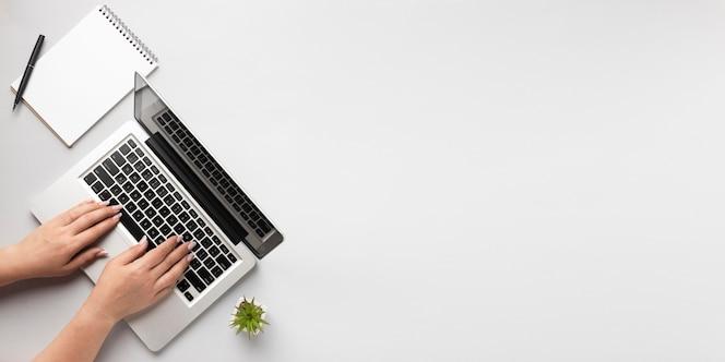 コピースペースでラップトップに書いているトップビューの人