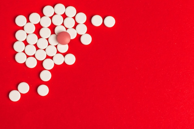 Top view of pharmaceutical medicine pills on red