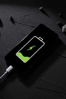 Top view. the phone,smartphone is charged,charging on a dark concrete table with stark shadows