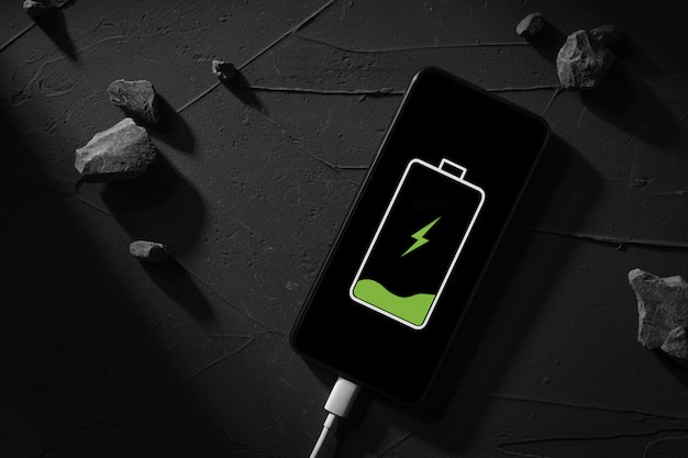 Top view. the phone, smartphone is charged, charging on a dark concrete