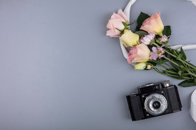 Top view of photo camera and flowers with ribbon on gray background with copy space
