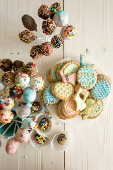 Top view photo of colorful cake pops and easter cookies