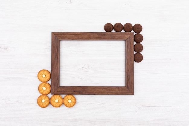 Top view photo frame with cookies and copy space on white surface
