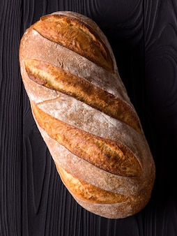 Top view photo of fresh baked bread on black wooden table.