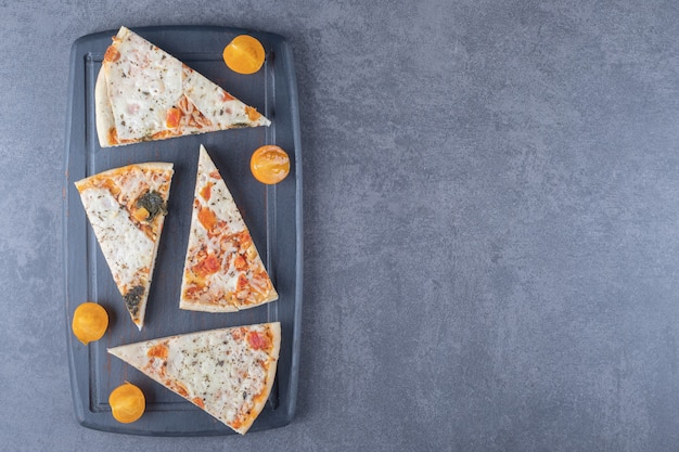 Top view photo of margarita pizza slices on grey wooden board.