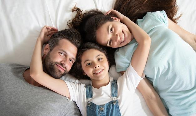 Фото вида сверху красивой счастливой семьи, лежащей на кровати и веселой