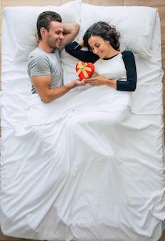 ハンサムな男性が彼のかわいい女性のためのギフトボックスを与えている間、愛の美しい幸せな若いカップルの上面写真は大きな白いベッドに横たわっています。