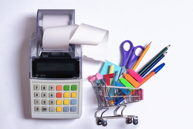 カラフルな文房具と白い背景に分離されたレシートテープ付きのレジのあるショッピングカートの上面写真。学校に戻るコンセプト