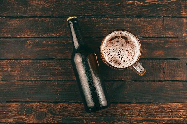 나무 배경 위에 병 맥주와 맥주 유리의 상위 뷰 사진