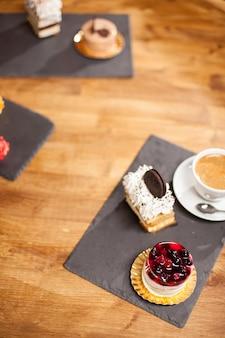 コーヒーショップの木製テーブルの上のさまざまなミニケーキの近くにおいしいビスケットとケーキの上面写真。上に美味しいフルーツとコーヒークリームが入った美味しいケーキ。