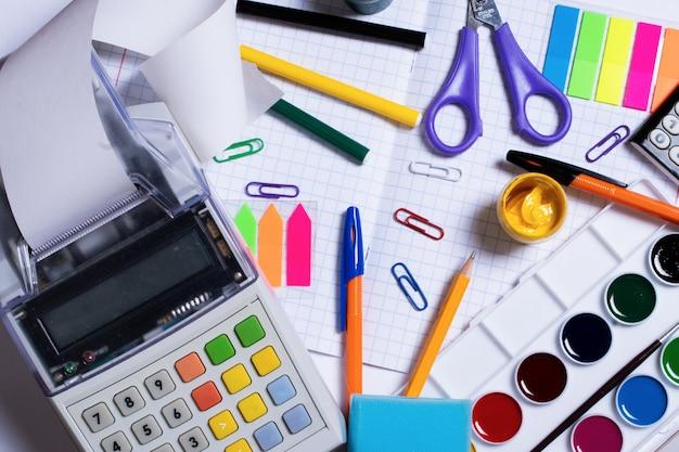 レシートテープと白い背景で隔離のカラフルな文房具とレジレコーダーの上面写真。フラットレイ、コピースペース。学校に戻るコンセプト