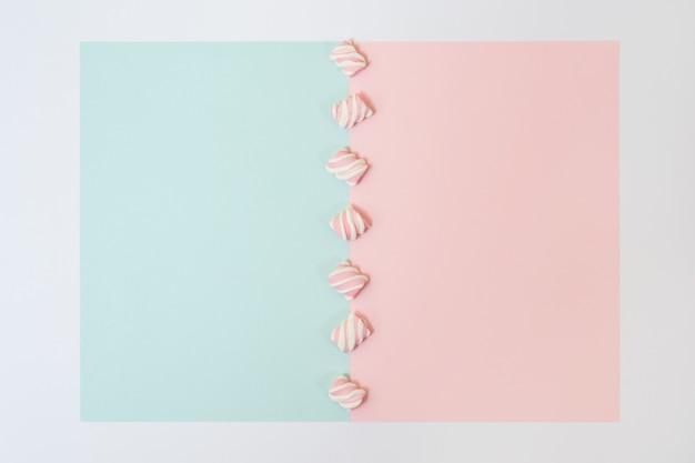 白いフレームの半分青い半分ピンクの背景の中央にマシュマロのカラフルなラインの上面写真