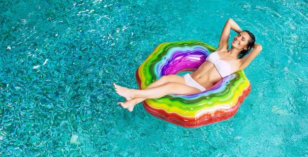 スイミングプールの膨脹可能なマットレスの上でビキニで日焼け興奮した女性を楽しんでいる上面写真。夏休み。ホテルのプールでリラックス