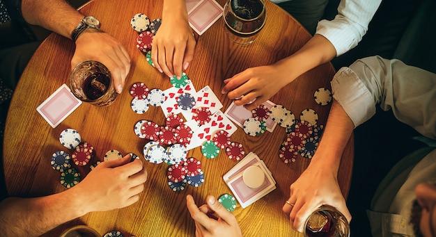 Фото взгляд сверху друзей сидя на деревянном столе. друзья веселятся во время игры в настольную игру.