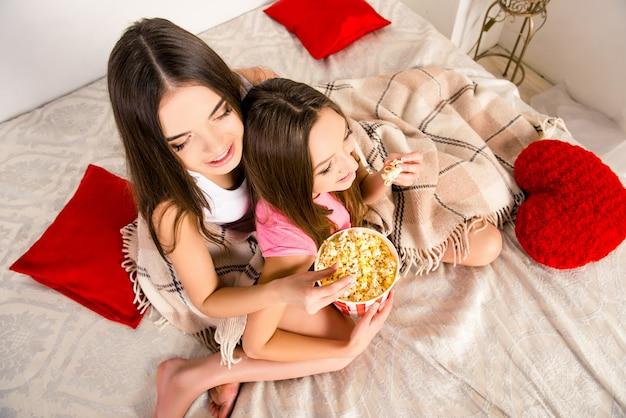 Фото девушек, сидящих на кровати с попкорном, вид сверху