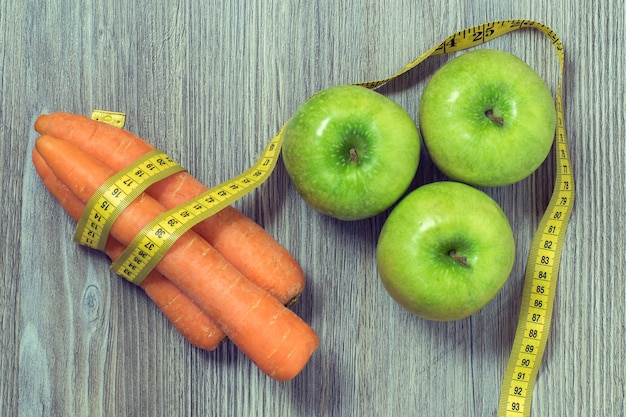 나무 테이블 배경에 녹색 사과 당근과 줄 자의 상위 뷰 사진