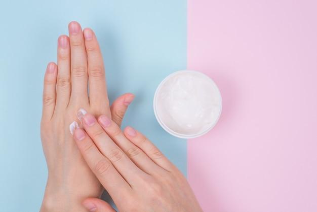 Фото вид сверху рук, применяющих крем и банку с кремом