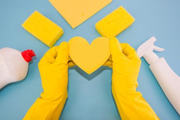 Вид сверху фото рук в желтых резиновых перчатках, держащих желтое бумажное сердце, разноцветные губки, вискозные тряпки, бутылки моющего средства на изолированном синем фоне