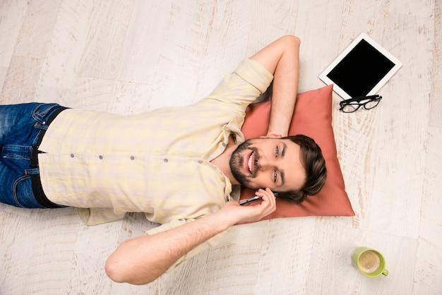 Фото человека, лежащего на полу и говорящего по телефону, вид сверху