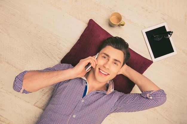 床に横になって電話で話している男性の上面写真
