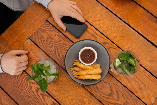 スマートフォンを使用してコーヒーテーブルで男の手の上面写真