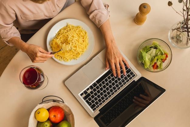 台所のテーブルでラップトップを使用しながらワインのグラスを保持している成熟した年配の女性の上面写真。フリーランス在宅勤務のコンセプト。