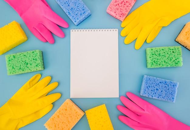 Фотография вида сверху блокнота, мочалки, вискозных ковриков, резиновых перчаток и белых бутылок немаркированного моющего средства на изолированном синем фоне