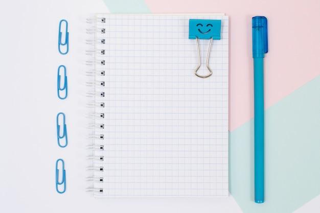 학용품의 상위 뷰 사진입니다. 분홍색 및 파란색 배경에 열린 나선형 노트북, 펜, 종이 클립 세트