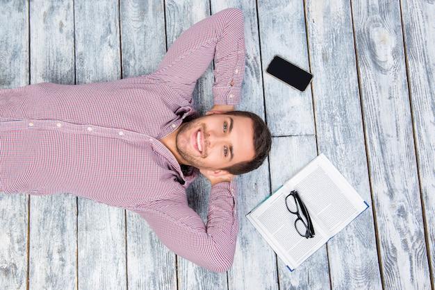 本、電話、メガネで床に横たわって笑顔の男の上面写真