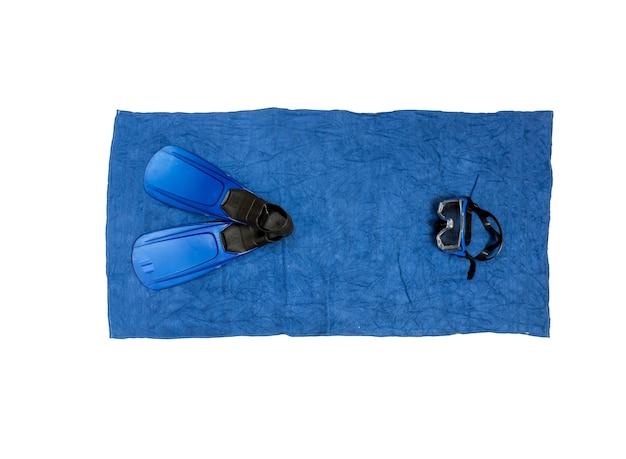 Фото вида сверху снаряжения для подводного плавания, лежащего на синем пляжном полотенце