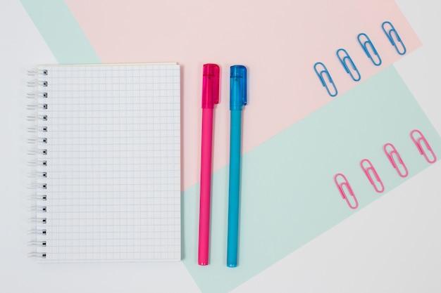 분홍색과 파란색 배경에 편지지의 상위 뷰 사진. 열린 빈 나선형 메모장, 펜 및 종이 클립 세트. 미니멀한 스타일