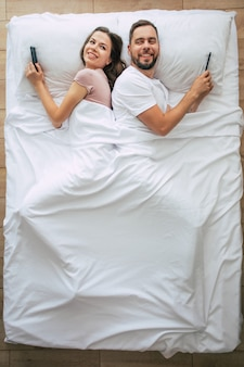 Фотография сверху: красивая женщина и красивый молодой человек используют смартфоны, лежа в большой белой кровати. переписываться онлайн. фотография выше пары.